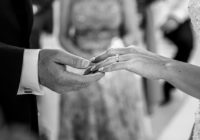 Black and white photo of bride and grooms hands during wedding ceremony captured by Adventure Photos