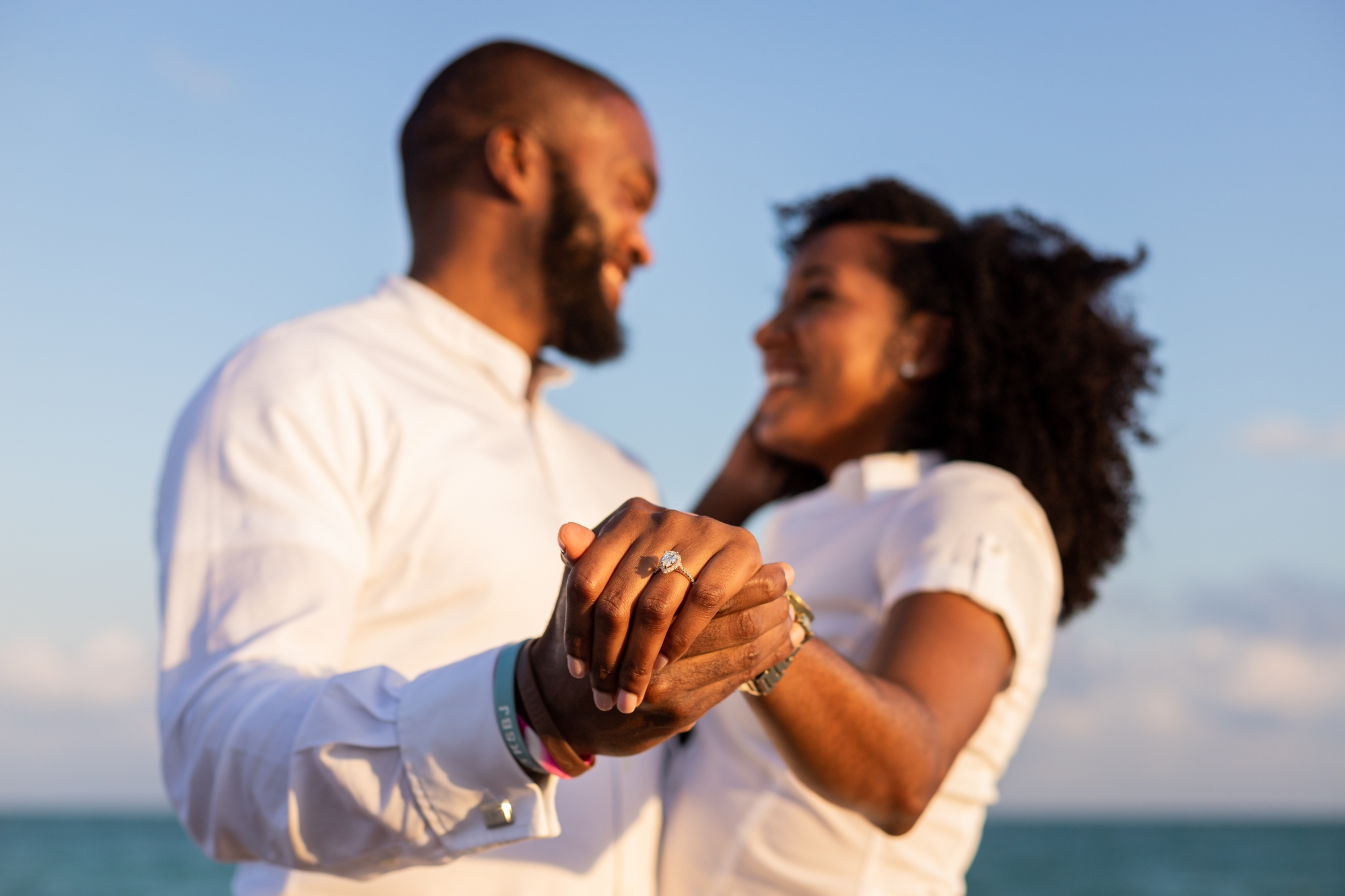 Engagement photo on beach, highlighting the engagement ring