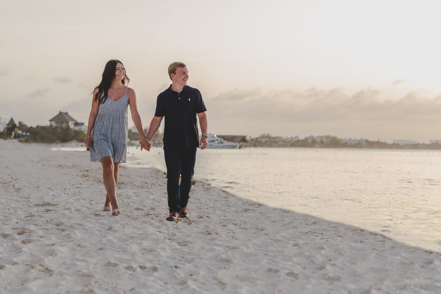 Marisa & Alex walking on beach at Dreams Sands Resorts during engagement photos