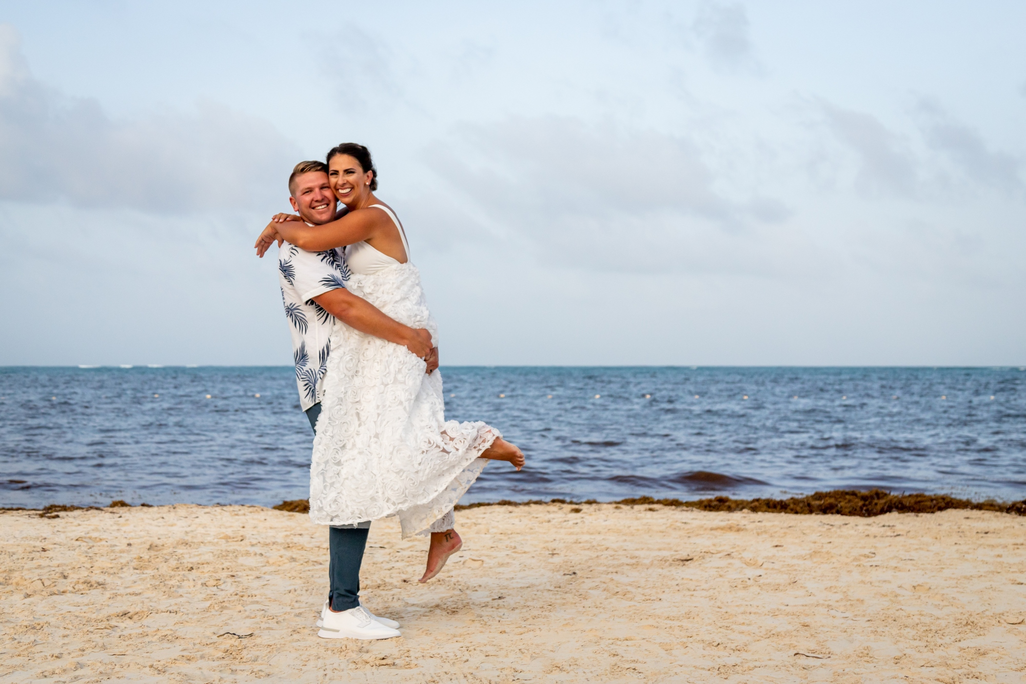 Newlyweds embracing on a beach in Cancun