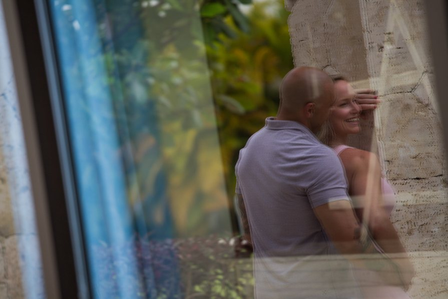 Reflection of Couple in Glass Window During Honeymoon Photo Shoot Captured by Adventure Photos