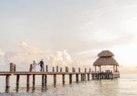 Newly married couple walking across a pier taken by photographer Hassler Raffoul Escareno.