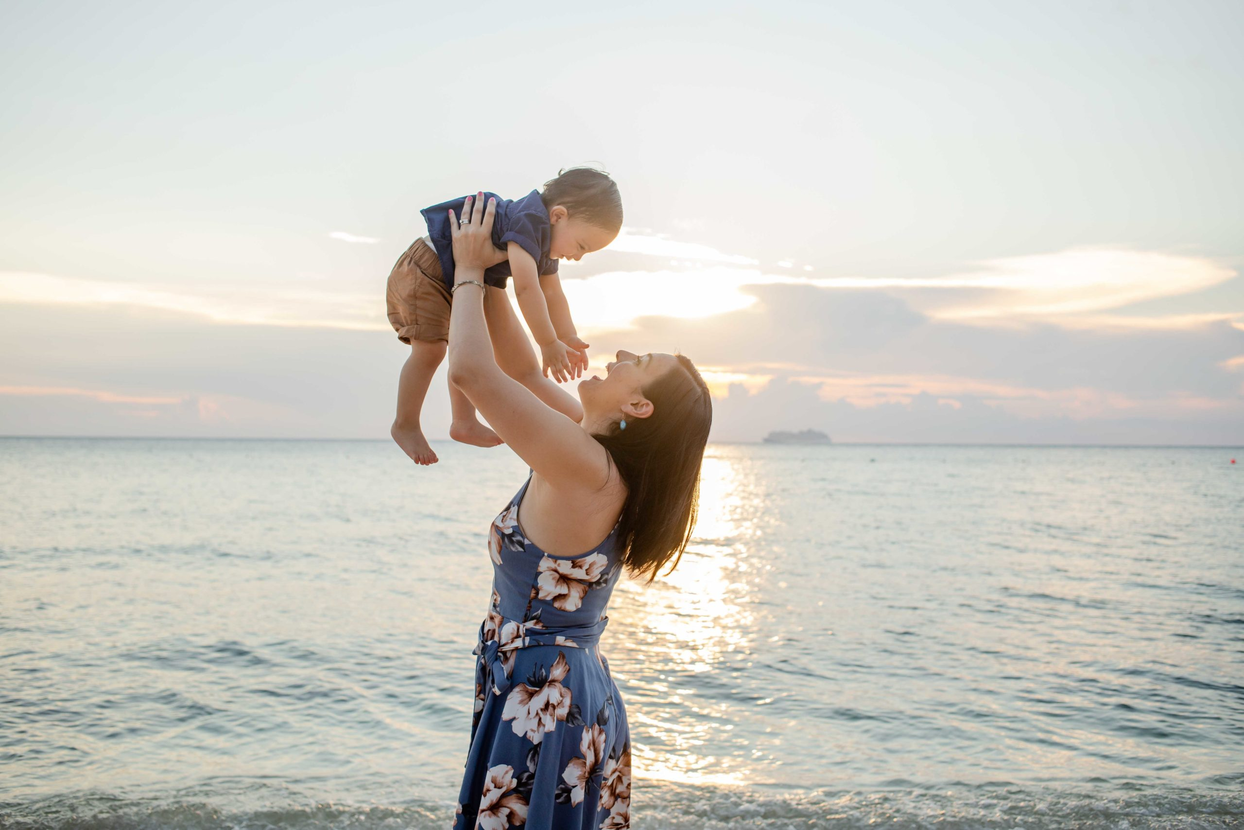 Mother holding her baby in the air with sea in the background. Taken by Hassler Raffoul Escareno.